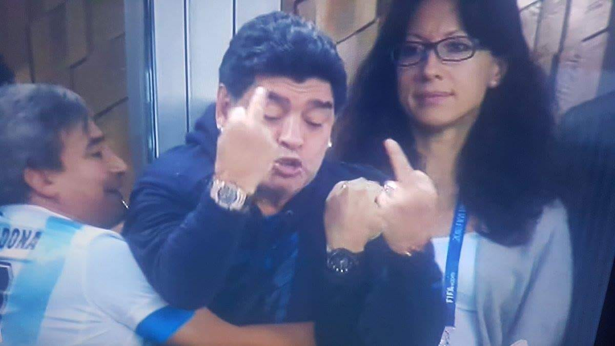 """Diego Armando Maradona e una serata sfrenata. Mentre si gioca in Nigeria – Argentina (match decisivo per il passaggio del turno a Russia 2018) va in scena un altro """"spettacolo"""", quello del Pibe de Oro tra eccessi, insulti e gestacci in una serata terminata anche con un lieve malore. ARGENTINA CHE SOFFERENZA: AGLI OTTAVI GRAZIE A MESSI E…. Si va dagli occhi spiritati al gol del vantaggio argentino segnato da Messi, alla camminata verso il proprio box sorretto a stento dagli amici e dagli uomini della propria cerchia, poi il gol decisivo di Marcos Rojo e il dito medio (doppio)"""