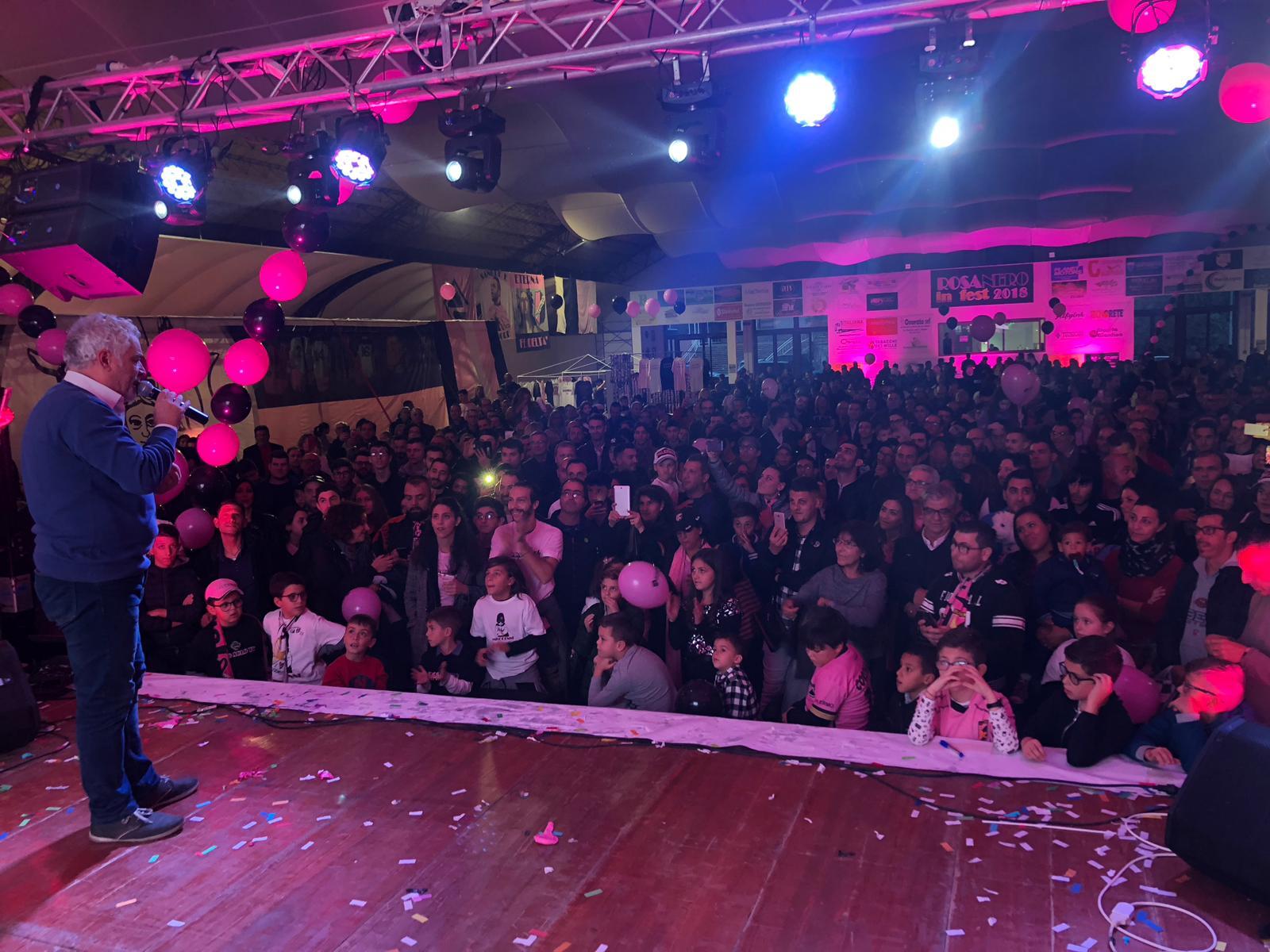 """Prosegue il programma di Rosanero in Fest, la festa dei colori rosanero e nella giornata di domenica, arriva uno dei momenti più sentiti e toccanti: sul palco sale Tony Sperandeo, per salutare il popolo rosanero, ma anche e soprattutto per il ricordo commosso di Gigi Burruano, scomparso un anno fa, tra storie e aneddoti legati al tifo per il Palermo LE FOTO DI ROSANERO IN FEST: LA VISITA DEI GIOCATORI Un momento toccante a cui Sperandeo aggiunge alla fine un appello a tutti i tifosi rosanero: """"Dobbiamo andare allo stadio, dobbiamo andare allo stadio… dobbiamo andare allo stadio! Giocare con"""